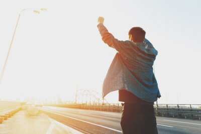 Naklejka Happy man is standing with his arms raised up. Happy man jumping for joy with his hands up. Happy young man at sunrise on a busy bridge cars. The concept of a free and joyful person