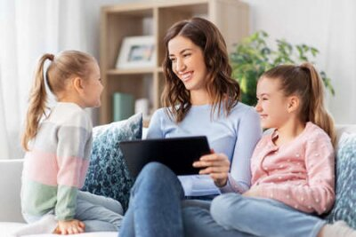 Naklejka happy mother and daughters with tablet pc at home