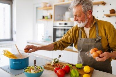 Naklejka Happy retired senior man cooking in kitchen. Retirement, hobby people concept