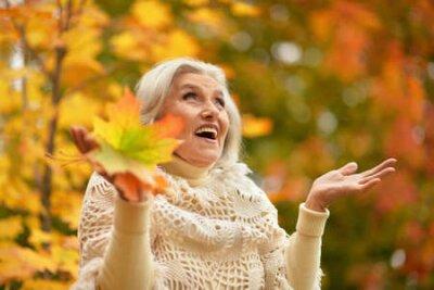 Naklejka Happy senior beautiful woman in autumn park