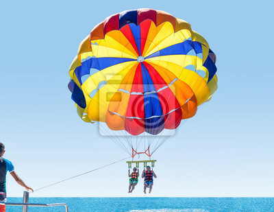 Naklejka Happy smiling couple Parasailing on Tropical Beach in summer. Newlyweds under parachute hanging mid air. Having fun. Tropical Paradise. Positive human emotions.