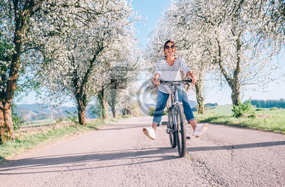Naklejka Happy smiling woman rides a bicycle on the country road under the apple blossom trees