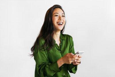 Naklejka Happy woman texting on a phone