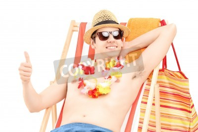Naklejka Happy young male enjoying on a beach chair and giving thumb up, isolated on white background
