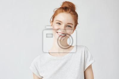 Naklejka Headshot portret szczęśliwa imbirowa dziewczyna z piegami uśmiecha się patrzejący kamerę. Białe tło.