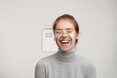 Naklejka Headshot przystojny szczęśliwa kobieta z przywiązanymi włosami czysta skóra i szeroki uśmiech zadowolony z oglądania w kamerze. Sincere żeński z pięknym wygląd noszenie casual ubrania izolowanych pona