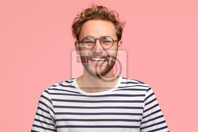 Naklejka Headshot zadowolonego modnisia ma zadowoloną minę, kręcone włosy i włosie, nosi okrągłe przezroczyste okulary i pasiastą koszulę, czuje radość po awansie w pracy, odizolowane na różowym tle