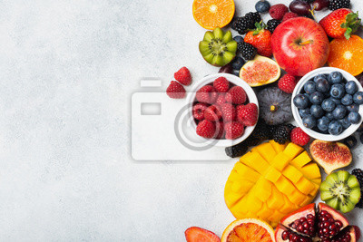 Naklejka Healthy raw rainbow fruits, mango papaya strawberries oranges passion fruits berries on oval serving plate on light kitchen top, top view, copy space, selective focus