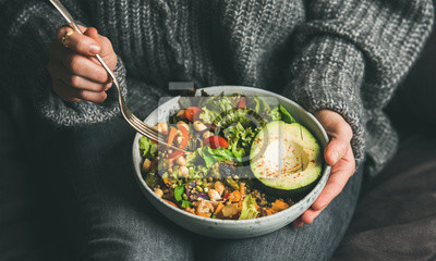 Naklejka Healthy vegetarian dinner. Woman in jeans and warm sweater holding bowl with fresh salad, avocado, grains, beans, roasted vegetables, close-up. Superfood, clean eating, vegan, dieting food concept