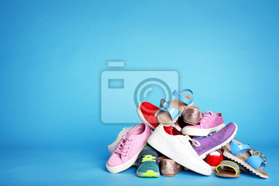 Naklejka Heap of different shoes on color background. Space for text