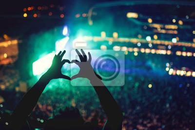 Naklejka Heart shaped ręce na koncercie, kochający artystę i festiwal. Koncert z oświetleniem i sylwetka człowieka korzystających z koncertu