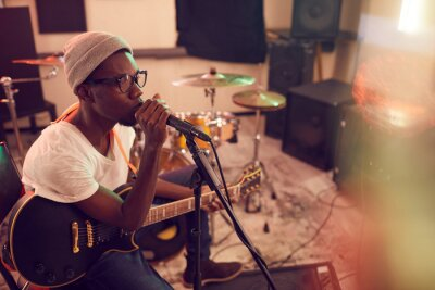 Naklejka High angle portrait of contemporary African-American man singing to microphone and playing guitar during rehearsal or concert with music band in recording studio, copy space