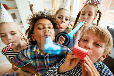 Naklejka High angle view at multi ethnic group of children blowing party horns at camera