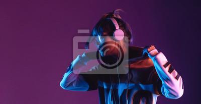 Naklejka Hipster igen teen pretty fashion girl model wear stylish glasses headphones enjoy listen new cool music mix stand at purple studio background in trendy 80s 90s club blue party light, profile view