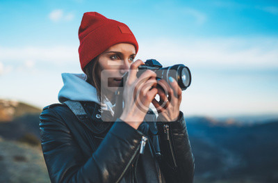 Naklejka hipster tourist girl hold in hands take photography click on modern photo camera, photographer look on camera technology, journey landscape vacation concept, sun flare mountain