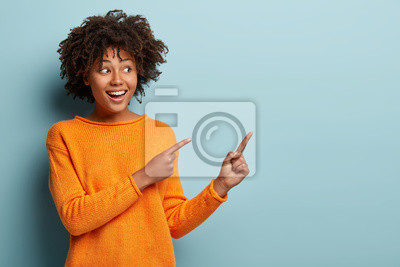 Naklejka Horizontal shot pleased dark skinned female with Afro haircut, points away with both fore fingers, shows blank space for your promotion, isolated over blue background. People, advertisement concept