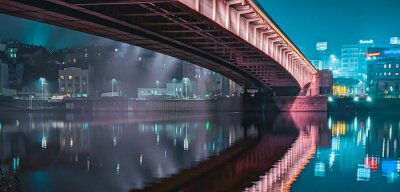 Naklejka Illuminated Bridge Over River By Buildings In City At Night