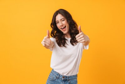 Naklejka Image of beautiful brunette woman wearing casual clothes winking and showing thumbs up at camera