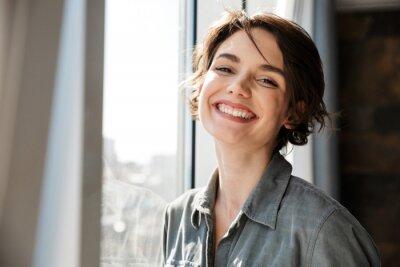 Naklejka Image of beautiful young joyful woman smiling and looking at camera