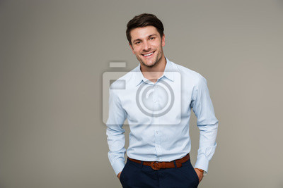 Naklejka Image of happy brunette man wearing formal clothes smiling at camera with hands in pockets