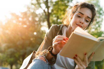 Naklejka Image of young woman smiling and reading book in green park