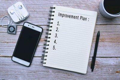 Naklejka Improvement plan text on wooden desk with accessories