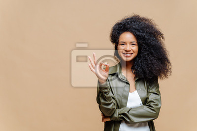 Naklejka Indoor shot of pleasant looking curly woman has pleasant smile, makes okay gesture, excellent sign, gives approval, dressed in fashionable leather shirt, isolated over brown wall, blank space on left