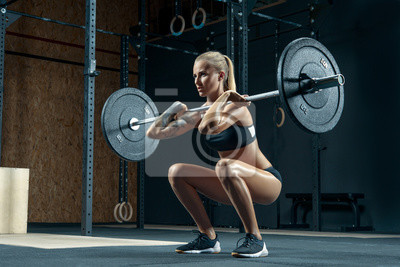 Naklejka Indoors shot of muscular young woman doing squats with barbell in a gym. Female bodybuilder doing workout Confident young blonde woman doing crossfit workout in gym Powerful attractive woman