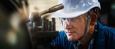 Naklejka industrial background of caucasian mechanics engineer operating lathe machine for metalwork in metal work factory