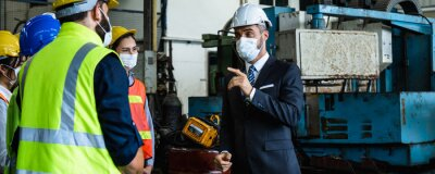 Naklejka Industrial engineers and businessman in suite and safety helmet wearing mask working in factory, planning, discussing and training workers with tablet in metalwork place , teamwork and team concept