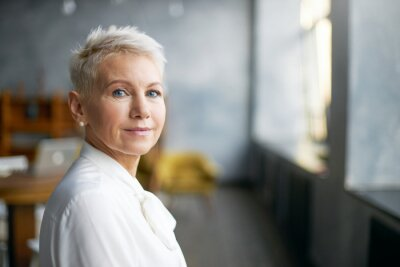 Naklejka Isolated image of beautiful stylish middle aged female entrepreneur with neat make up going to business meeting, standing against office interior background, looking at camera with confident smile