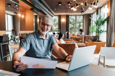 Naklejka Italy, Smiling man working at table in creative studio