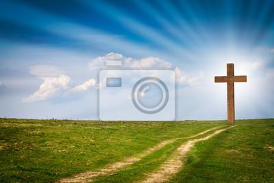 Naklejka Jezus Chrystus krzyż, drewniany krzyż na scenie z błękitne niebo wiosny, zielone łąki, jasne światło, promienie, chmury. Chrześcijański drewniany krzyż na polu z zieloną trawą i ścieżki prowadzącej do