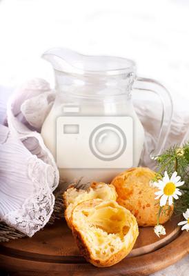 Jug z mleka, chleba i dzikie kwiaty na białym tle