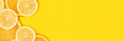 Naklejka Juicy citrus on a yellow background. Bright vitamin photo. Copy space, web-banner format.