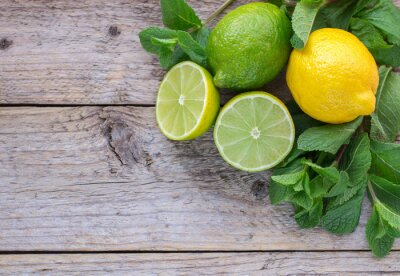 Naklejka Juicy dojrzałe owoce cytrusowe na starym drewnianym stole - limonki, cytryny i mięty