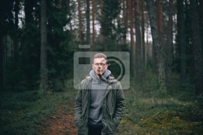 Naklejka Kaukaski młody człowiek w lesie w zielonej kurtce.