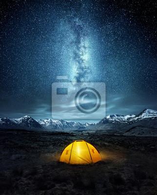 Naklejka Kemping na pustyni. Rozbity namiot pod świecącymi gwiazdami nocnego nieba drogi mlecznej z śnieżnymi górami w tle. Kompozyt fotograficzny krajobrazowy.