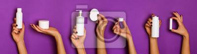 Naklejka Kobiece ręce trzymając butelki białe kosmetyki - balsam, krem, serum na fioletowym tle. Transparent. Pielęgnacja skóry, czyste piękno, koncepcja leczenia ciała