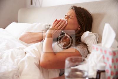 Naklejka Kobieta cierpi na zimno leżąc w łóżku z tkanek