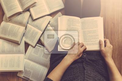Naklejka Kobieta czyta kilka książek na podłodze