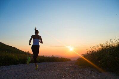 Naklejka kobieta działa na górskiej drodze na zachód słońca latem