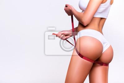 Naklejka Kobieta mierzy pośladki, tracąc na wadze