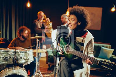 Naklejka Kobieta mieszanej rasy śpiewa i gra na gitarze, siedząc na krześle ze skrzyżowanymi nogami. W tle perkusista, saksofonista i gitarzysta basowy.