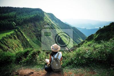 Naklejka kobieta podróżnik trzyma kapelusz i patrząc na niesamowite góry i las, koncepcja podróży wanderlust, miejsce na tekst, atmosferyczny epicki moment, azory, porthal, ponta delgada, sao miguel