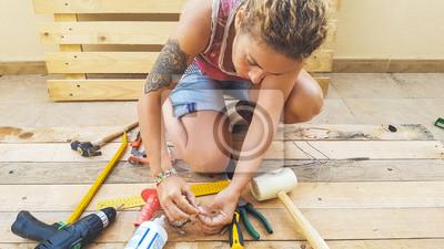 Naklejka kobieta pracująca na zewnątrz ze sprzętem kuchennym buduje meble lub coś do domu z recyklingu palet drewno sosnowe. zrób to sam koncepcja hobby