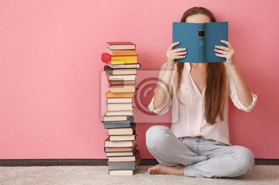 Naklejka Kobieta siedzi na podłodze i gospodarstwa książki przed twarzą na różowym tle