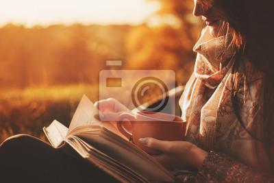 Naklejka kobieta siedzi przy drzewie w parku jesiennym i posiada książkę i filiżankę z gorącym napojem w rękach. Dziewczyna czyta książkę