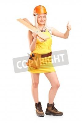 Naklejka Kobieta stolarz trzyma kilka desek i podając kciuk w górę na białym tle