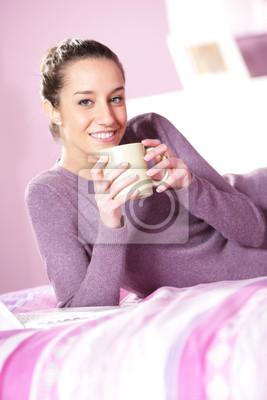 kobieta trzyma filiżankę kawy w łóżku
